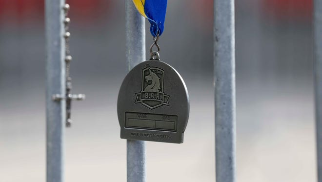 A finisher's medal and a cross hang on a barricade at the intersection of Berkeley and Boylston Streets the day after a bombing near finish line of the 2013 Boston Marathon. There are plans to honor all those involved one year after the events.