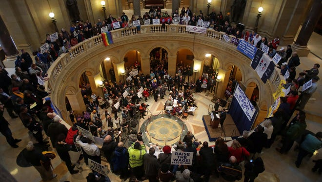 Demonstrators rally at the Minnesota state Capitol, calling for lawmakers to raise the minimum wage in February. Gov. Mark Dayton signed a law to raise the wage Monday.