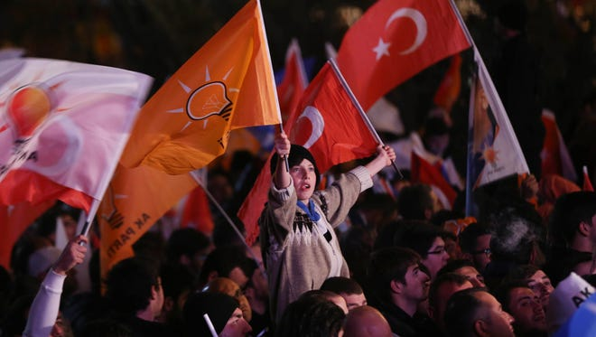 Supporters of Turkey's ruling AK party (AKP) cheer as they follow the election's results in front of the party's headquarters in Ankara.
