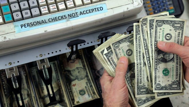 A clerk counts cash at the register at a store in East Aurora, N.Y.
