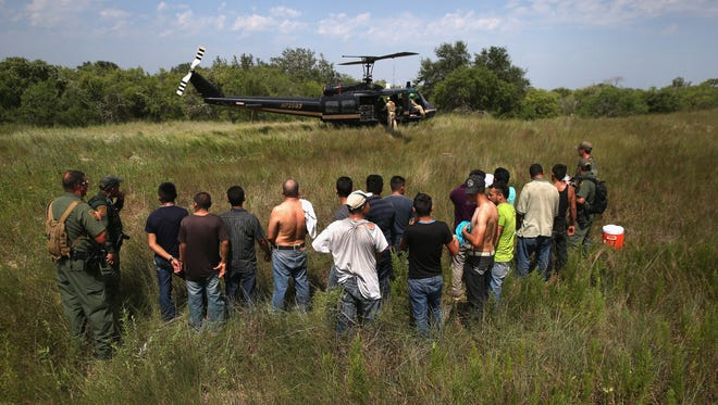 U.S. Border Patrol agents guard undocumented immigrants before sending them to a processing center on July 22, 2014 near Falfurrias, Texas. Thousands of immigrants, many of them minors, have crossed illegally into the United States this year, causing a humanitarian crisis on the U.S.-Mexico border. Texas Governor Rick Perry announced that he will send 1,000 National Guard troops to help stem the flow.