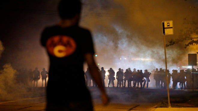A man watches as police walk through a cloud of smoke during a clash with protesters Wednesday in Ferguson, Mo.