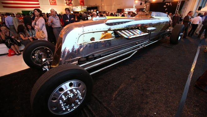 Onlookers admire the 30 foot long Packard Royal V12 at the McCall Motorworks Revival in Monterey, Calif.