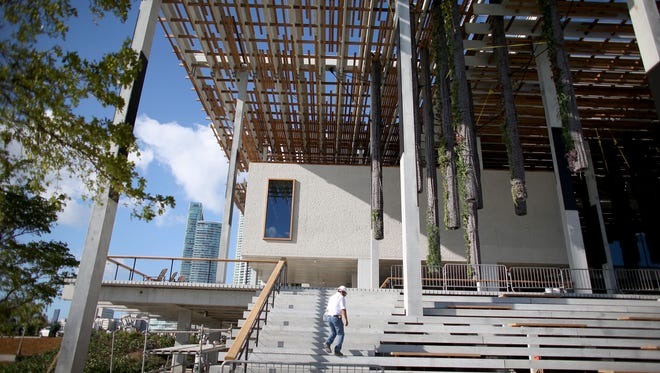A construction worker walks up the stairs to the back terrace as they continue to put finishing touches on a museum in Miami.