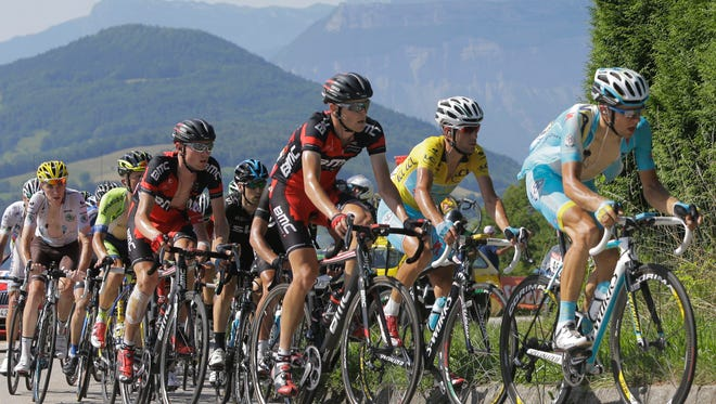 Tejay van Garderen of the U.S., fourth from left with bandaged right leg, and stage winner Italy's Vincenzo Nibali, wearing the overall leader's yellow jersey, second right, climb towards Chamrousse during the thirteenth stage of the Tour de France cycling race over 197.5 kilometers (122.7 miles) with start in Saint-Etienne and finish in Chamrousse, France, Friday, July 18, 2014.