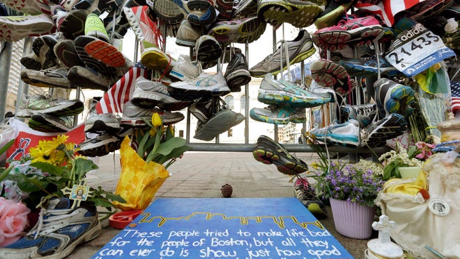 In this April 25, 2013 photo, running shoes and other items adorn a makeshift memorial near the Boston Marathon finish line in Boston's Copley Square. Thousands of items from the original memorial for marathon bombing victims are going on display at the Boston Public Library in April 2014 to mark the anniversary of the attacks.