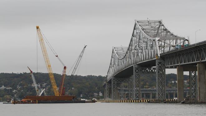 Boats and barges line up along side of the old Tappan Zee Bridge on Oct. 16, 2013.  The official assembling of the new bridge has commenced. ( Ricky Flores / The Journal News )