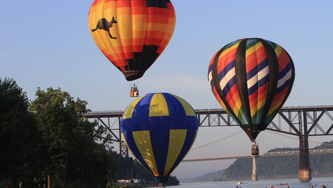 Hot air balloons take off from the banks of the Hudson River in Poughkeepsie during the annual Dutchess County Balloon Festival July 6, 2013. In the background is the Walkway Over the Hudson and the Mid-Hudson Bridge.