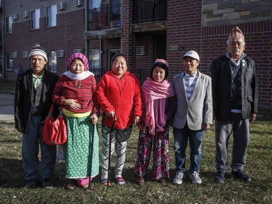 Refugees from Bhutan gather for a group photo from the yard at the Deer Ridge Apartments in Des Moines on Saturday, Dec. 2, 2017. The apartments are not on any public transportation routes, and with limited means of mobility, many refugees in the complex walk miles to buy groceries.