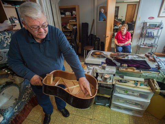 Ken Pugh, left, holds and points at a guitar he is building as his wife, Norene Pugh watches inside of his shop on Monday, Jan.18, 2015 in Waynesboro, Pa. Pugh has been building instruments since 1965.