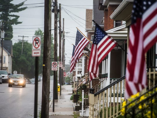 A vehicle moves through the rain on West Hanover Street near a row of flags Monday. Despite the overcast skies and intermittent showers, Hanover's public fireworks display still went off as scheduled.