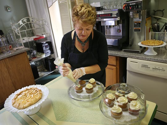 Small business owner and village resident Jo Matela finishes a batch of pumpkin cupcakes in the kitchen at her Red Bird Cafe in Brockport Wednesday, Oct. 5, 2016.