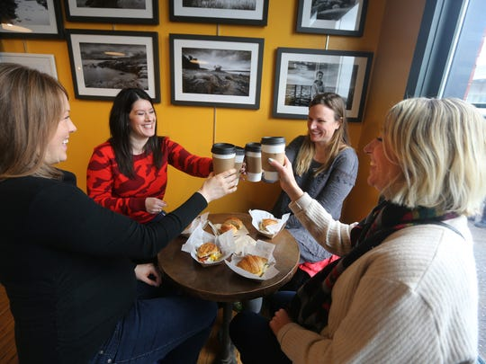 Adena Miller, in red, and friends, from left, Brittany Buffington, Amanda Birchenough and Alma Vieru, enjoy breakfast at the Flour City Bread Co. at the Rochester Public Market.