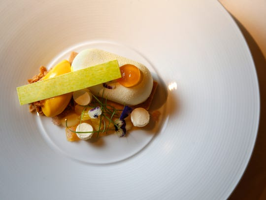 Coconut sabayon dessert, featuring coconut meringues, macadamia nut crispy, mango sorbet, white chocolate, lime, and bergamot jelly, pictured, Monday, March 6, 2017, at Orchids at Palm Court restaurant in Cincinnati.