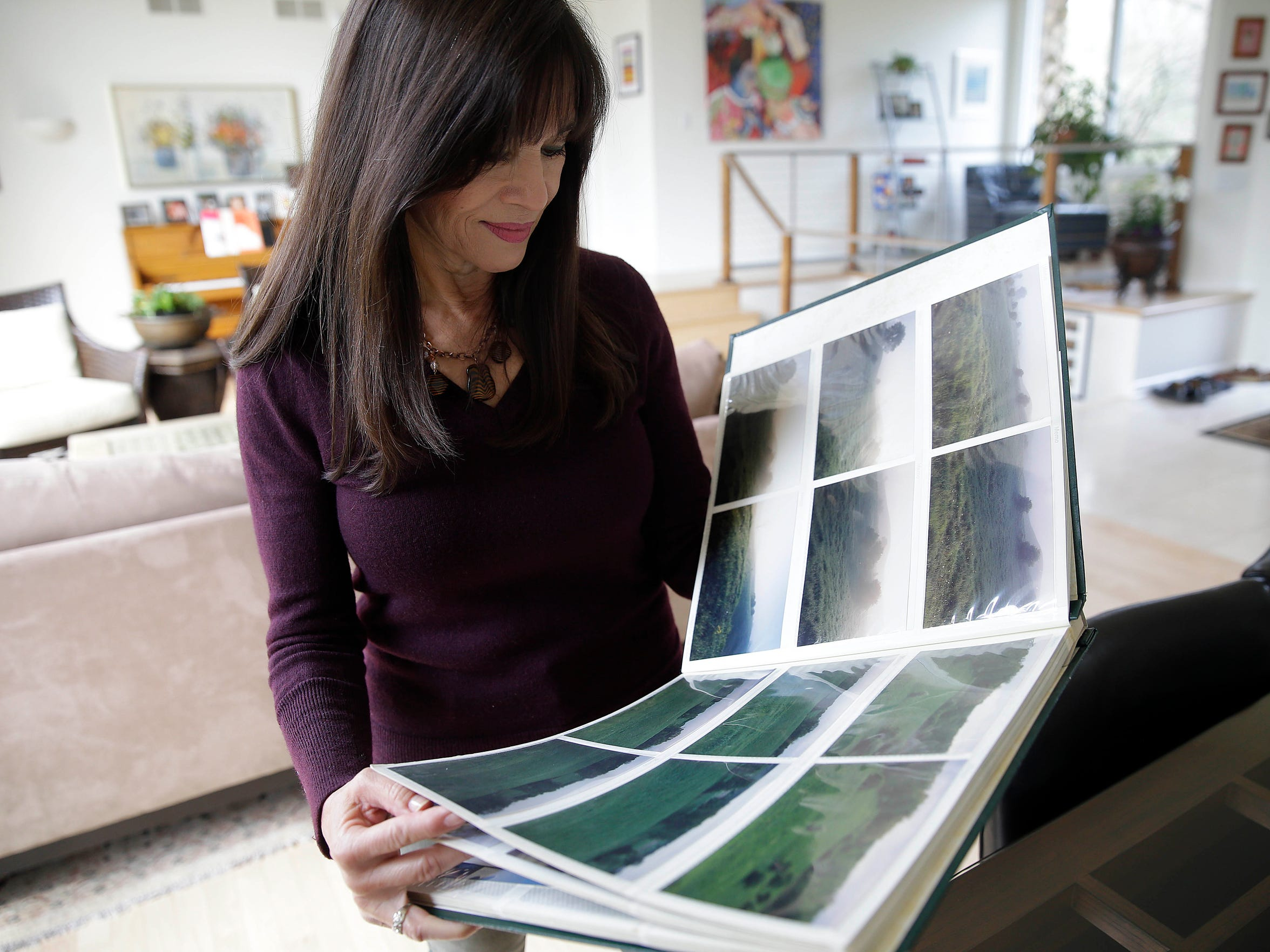 Lillian Williamson looks at a scrapbook she kept of photos of the land that would become Erin Hills.
