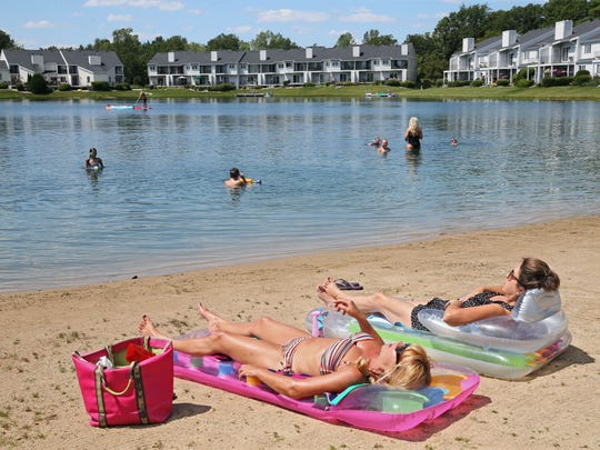 Tuckaway Shores resident Sue Czerwinski (foreground) and guest Lisa Herriges sun on the beach while children swim in the private lake that meanders through the complex in Franklin. Czerwinski is among the residents who are concerned that development of a large middle school on an adjacent property could negatively impact the lake.