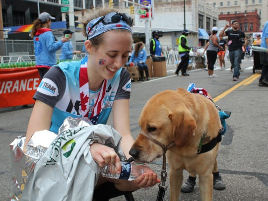 Meagan Giancarlo of Beverly Hills helps her service dog, Diesel, rehydrate after finishing international half-marathon during the 40th Detroit Free Press/Chemical Bank Marathon in Detroit on Sunday, Oct. 15, 2017.