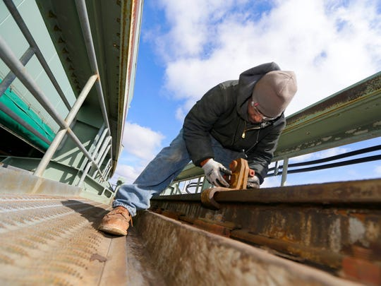 Derek Strickland, an ironworker with Price Erecting, secures a clamp used to temporarily lift the track in order to replace the roof track rail rubber that controls the vibrations and sound as the roof is moving.