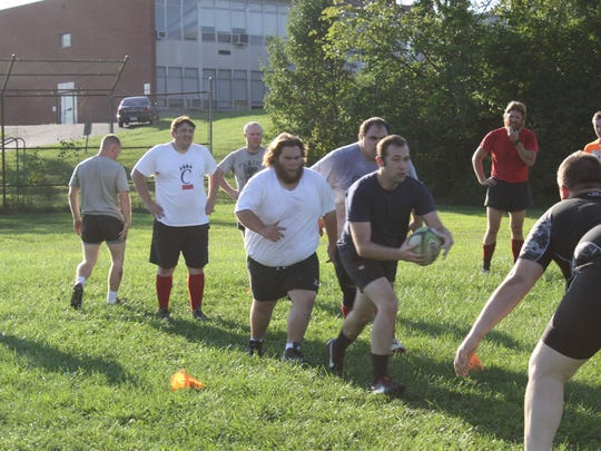 "During a Northern Kentucky Grubs rugby practice drill, Bryan Snapp takes the ball into contact with Mike Ramsey and Chris ""McRib"" Cahill in support."
