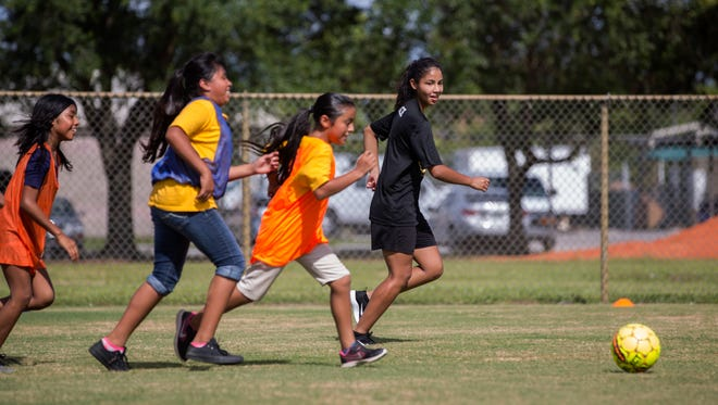 Maria Rodriguez plays in a soccer game with fifth- and sixth-grade girls from Immokalee Community School during practice at Immokalee Community Park on July 6, 2017. Rodriguez is not eligible for federal financial aid because she is a Deferred Action for Childhood Arrivals (DACA) recipient, so the community raised money to help her pay for school. She will be attending Broward College and will play soccer.