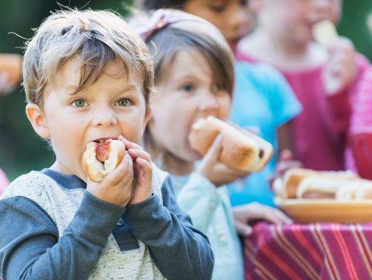 Little boy eating a hotdog at a cookout