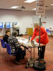 Dodie Berg signs in before voting at the Mead Library
