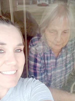 LaDonna Llamas takes a selfie with her grandmother Peggy Thompson who is a resident of Kenwood Plaza in St. John. Because of the coronavirus, care facilities like Kenwood Plaza have gone on lock down and no face to face visits are allowed so phones have been made available for family to visit with their relative through windows.