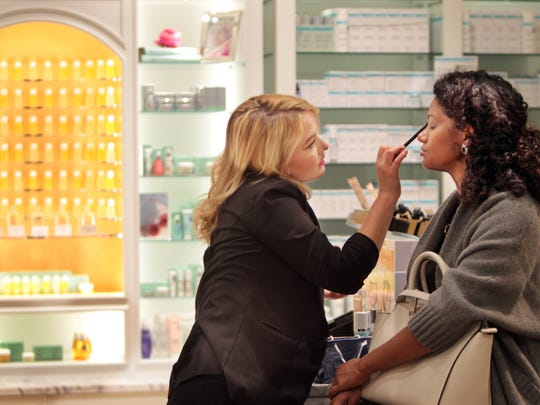 Tara Filliater (left), store manager for Bluemercury in Macy's at Kenwood Towne Center, applies makeup to Sara Girmay of Liberty Twp. during a makeover at the new store.
