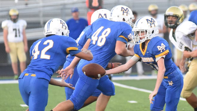 Junior Bomber quarterback Brody Patterson hands off to Xzavier Anderson during Mountain Home's 33-13 loss to Greene County Tech on Thursday night.