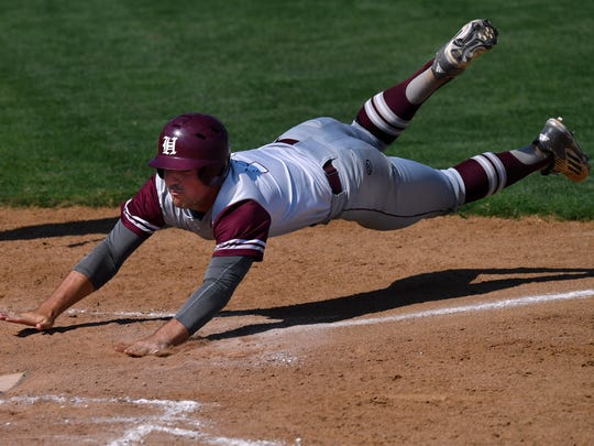 Hawley's Quay Stokes dives for home plate during Friday's game against New Deal. New Deal won, 4-3.