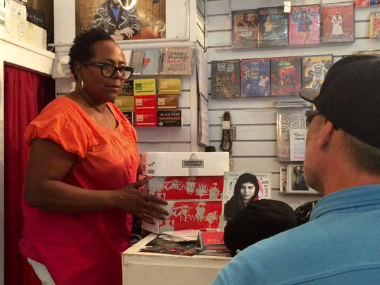Zana Smith, the owner of Spectacles in Detroit, waits on long-time customer Mark Walls.