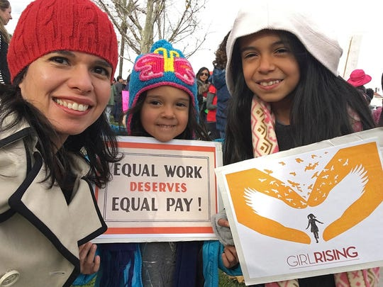 In this Jan. 21, 2017 photo provided by Aileen Rizo,  Rizo, along with her daughters Diana Acosta, 10, center, and Vivan Acosta, 6, right, attend the national Women's March in Fresno, Calif.