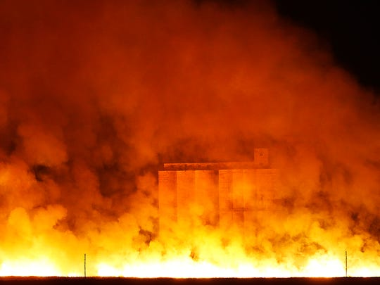 Flames and smoke envelope a grain elevator in Sitka,