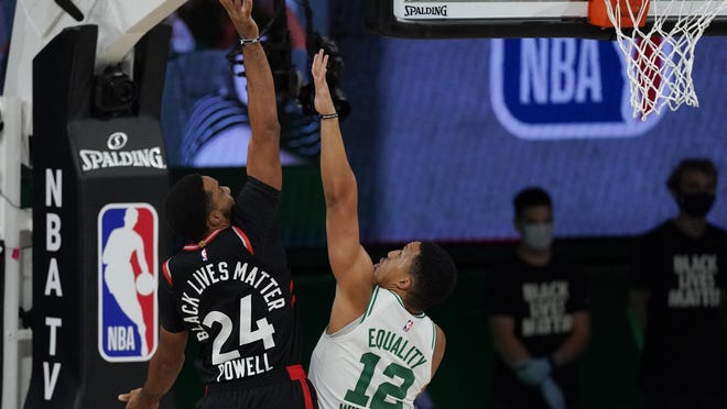 The Celtics' Grant Williams tries to defend against the shot of the Raptors' Norman Powell during Saturday's Eastern Conference playoff game. Of the seven rookies on Boston's roster, Williams has seen the most playing time.