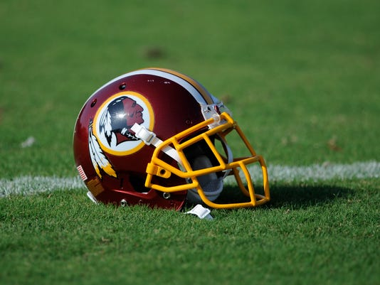 """A Washington Redskins football helmet lies on the field during NFL football minicamp, Wednesday, June 18, 2014, in Ashburn, Va. The U.S. Patent Office ruled Wednesday, June 18, 2014, that the Washington Redskins nickname is """"disparaging of Native Americans"""" and that the team's federal trademarks for the name must be canceled. The ruling comes after a campaign to change the name has gained momentum over the past year.  (AP Photo/Nick Wass)"""