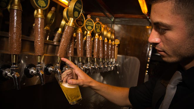 De La Vega's Pecan Grill and Brewery bartender Drew Dougherty pours a pint of the brewery's Light American lager, June 9, 2016. The company announced Thursday that it would be building a bottling and brewing facility to Las Cruces. Currently, those operations take place in Moriarty.