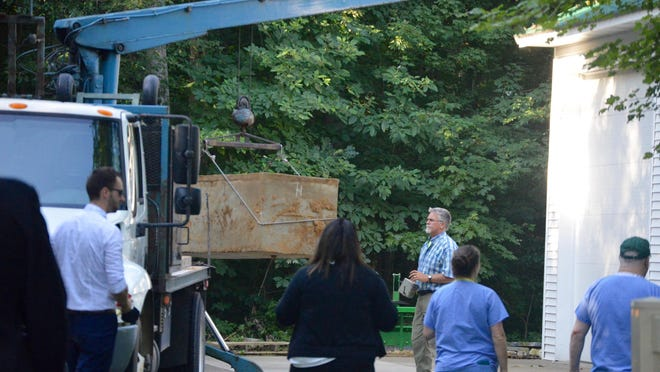 The burial vault of a young woman strangled in 1967 is lowered from a truck after being exhumed Wednesday, July 29, at Blendon Cemetery. Police and investigators are working to identify the remains in hopes of solving the cold case.