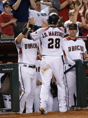 Diamondbacks teammates greet JD Martinez (28) after he scored against the Rockies in the fourth inning at Chase Field in Phoenix, Ariz. on Sept 11, 2017.