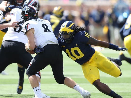 Michigan's Devin Bush pressures Cincinnati's Hayden Moore in the first quarter Saturday, September 9, 2017 at Michigan Stadium.
