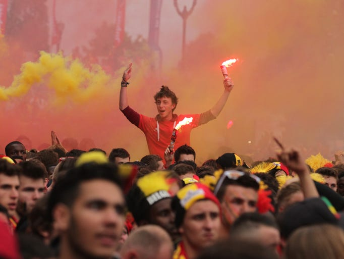 A fan of the Belgian national soccer team holds a flare after watching their quarterfinals soccer match against Argentina, broadcast on a video screen in front of the King Baudouin stadium in Brussels, Saturday, July 5, 2014. Argentina defeated Belgium 1-0. (AP Photo/Yves Logghe)
