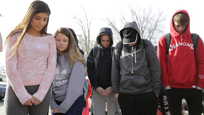 Students at Menasha High School pause for a moment of silence Wednesday morning as they participate in the National School Walkout Day.