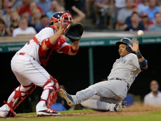 New York Yankees' Starlin Castro scores on a hit by New York Yankees' Chase Headley in the sixth inning of a baseball game against the Cleveland Indians, Thursday, July 7, 2016, in Cleveland. Catcher Cleveland Indians' Chris Gimenez waits for the ball. (AP Photo/Tony Dejak)
