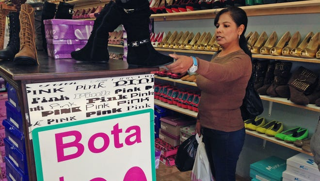 Martha Isabel Velasquez looks at a pair of boots while shopping in downtown Nogales, Ariz. Velasquez says she waited two hours in line to cross by foot over from Nogales, Sonora, Mexico, to go shopping.