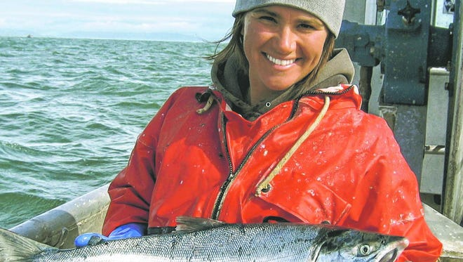 Heidi Dunlap with a freshly caught salmon. Hazardous as it is, catching the fish is just the beginning.
