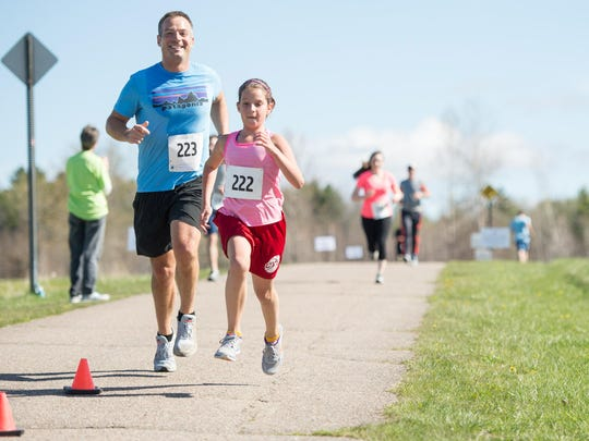 Adam and Maddie Bunting of Williston near the finish of the VNA Vermont Respite House 5K Fun Run & Jiggety Jog in Williston on Saturday.