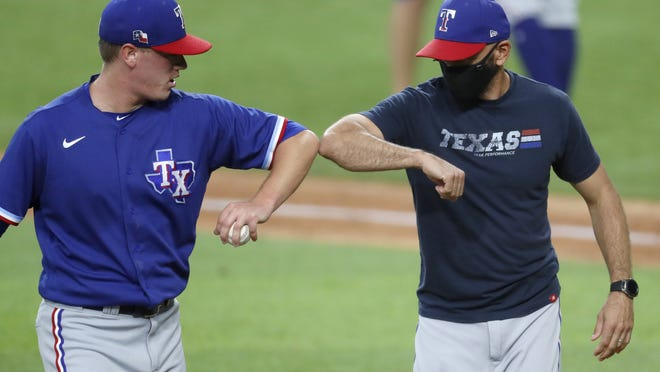 In what could be a new normal in sports, Kolby Allard, left, of the Rangers bumps elbows with manager Chris Woodward after he was done pitching in an intrasquad game on Monday.
