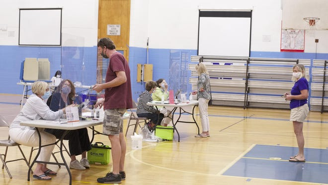 Voters practice social distancing while voting at Gaudet Middle School during September's primary election. Voting on election day is just one option for casting a ballot in R.I.