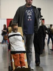 Dan Nichols of Toledo pushes his son Milo, 7, who is dressed as Hannibal Lecter at Motor City Comic Con at the Suburban Collection Showplace in this 2017 file photo. The event returns to Novi this weekend.