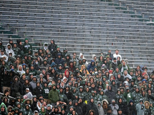 After a three-hour delay, Michigan State fans cheer in the rain in the second quarter during MSU's win over Penn State.