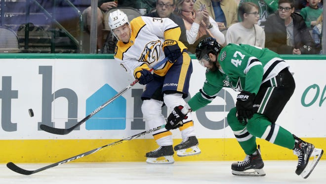 Predators left wing Viktor Arvidsson (33) moves the puck against Stars right wing Alexander Radulov (47) during the first period of a game Dec. 23.
